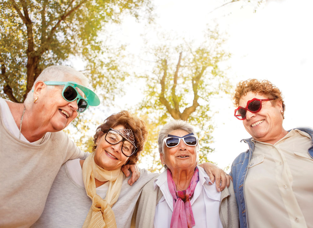 Four older women stand close together outside and pose in funny sunglasses