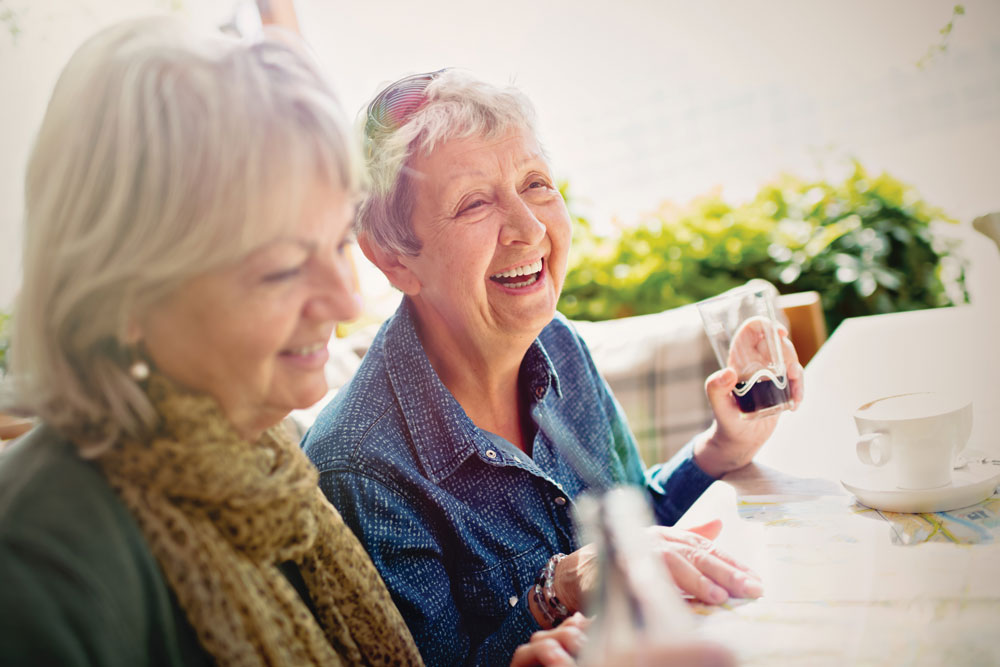 Two older women smile and share beverages at an outdoor table