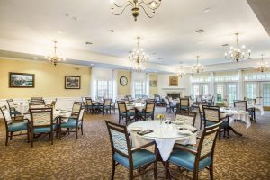 Large carpeted dining room with numerous table and chair sets, chandeliers, and decor