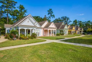 Row of pastel colored resident cottages with large yard and garden space and pathways