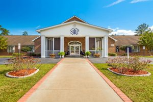 Direct view of pathway lined with bushes and grass leading to main entrance of Southern Pines Senior Living
