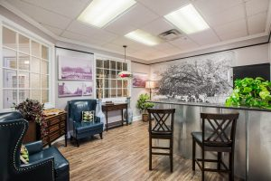 Ice cream bar with arm chairs, bar and chairs, windows, and various decor
