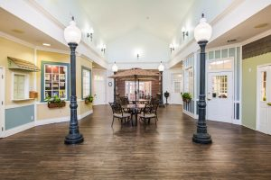 Indoor lobby designed to resemble a street with storefronts, table and chairs, and lamp posts
