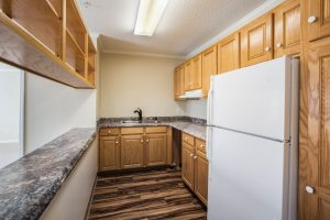 Kitchen with refrigerator, hardwood flooring, countertops, sink, and numerous overhead cupboards