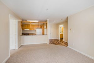 Open, unfurnished carpeted living area with view of kitchen