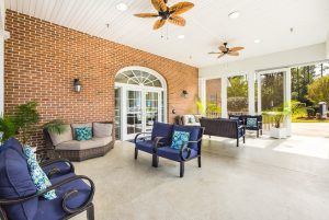 Porch with outdoor furniture and cushions, overhead fans, and potted plants