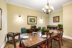 Private dining room with table, chairs, table settings, overhead light fixture, cabinets, and wall decor